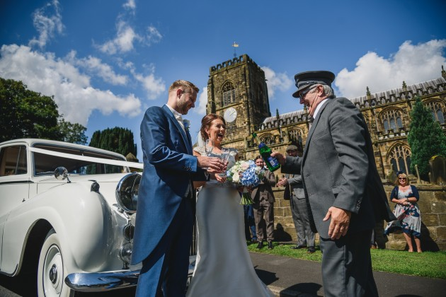 Stan-Seaton-Photography-bride-and-groom-opening-champagne-at-the-church