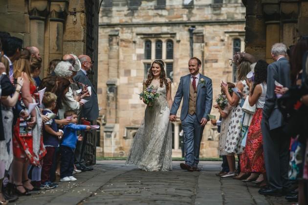 052 Durham-Castle-Wedding-Photographer-Stan-Seaton-bride-and-groom-walking-through-the confetti.JPG