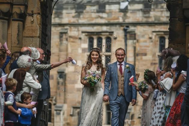 053 Durham-Castle-Wedding-Photographer-Stan-Seaton-bride-and-groom-walking-through-the-confetti.JPG