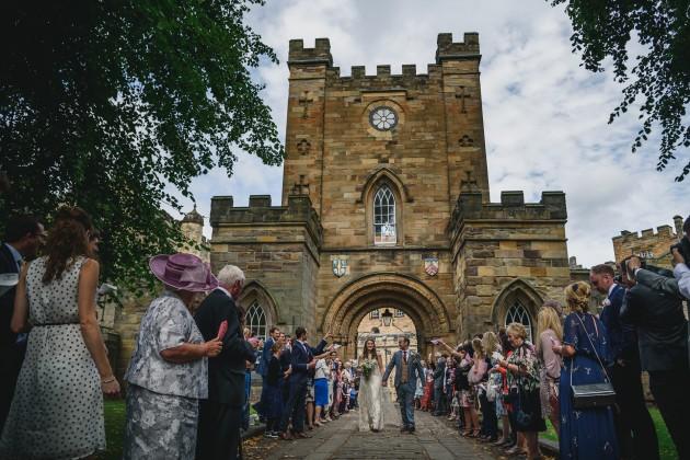 054 Durham-Castle-Wedding-Photographer-Stan-Seaton-bride-and-groom-walking-through-the-confetti..JPG